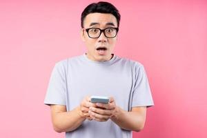 portret van aziatische man met smartphone op roze achtergrond foto