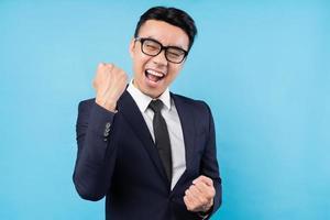 portret van een opgewonden Aziatische zakenman op een blauwe achtergrond foto