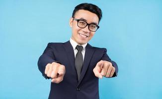 Aziatische zakenman die een pak draagt dat op een blauwe achtergrond wijst foto