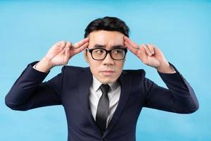 Aziatische zakenman denken over werk op blauwe achtergrond foto
