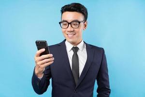 Aziatische zakenman die een pak draagt met een smartphone op een blauwe achtergrond foto