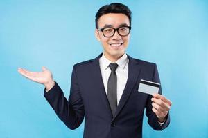 Aziatische zakenman met bankkaart op blauwe achtergrond foto
