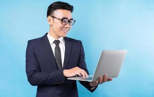 Aziatische zakenman die pak draagt en laptop op blauwe achtergrond gebruikt foto