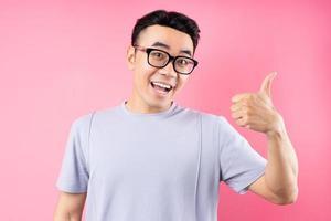 portret van aziatische man die zich voordeed op roze achtergrond met veel expressie foto