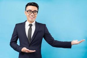 portret van aziatische zakenman die pak op blauwe achtergrond draagt foto