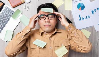 Aziatische man liggend op stapel papieren en moe van het werk foto