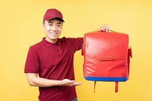 Aziatische bezorger met een rood uniform poserend op gele achtergrond foto