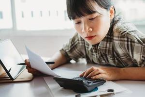 jonge aziatische vrouw berekent de te betalen belasting foto
