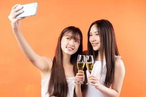 twee mooie jonge Aziatische meisjes die wijnglazen op oranje achtergrond opheffen foto