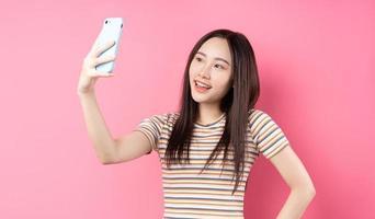 jonge aziatische vrouw die smartphone op roze achtergrond gebruikt foto