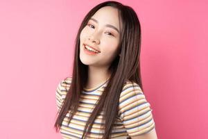 jonge aziatische vrouw die zich voordeed op roze achtergrond foto