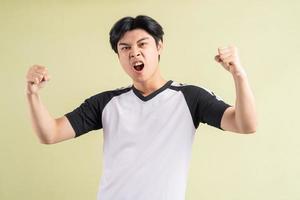 de Aziatische man schreeuwde het uit van een triomfantelijke uitdrukking foto