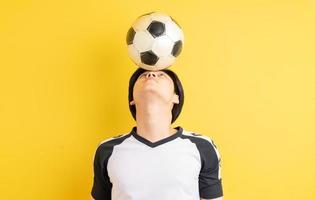 de Aziatische man stuitert de bal met zijn hoofd his foto