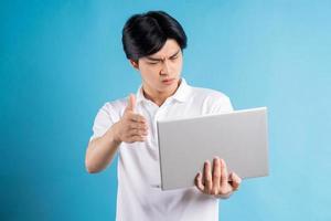 de Aziatische man voert een videogesprek en maakt ruzie over zijn laptop his foto