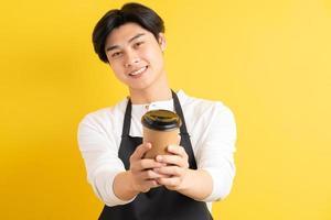 portret van mannelijke ober met papieren beker in de hand op gele achtergrond foto