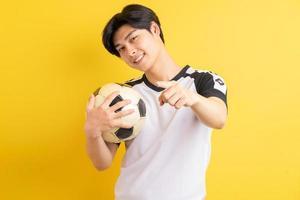 de Aziatische man hield de bal vast en wees met zijn hand? foto