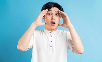 de Aziatische man hield zijn hoofd met zijn handen in ongeloof dis foto