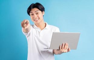 de Aziatische man hield zijn laptop vast en wees met zijn hand? foto