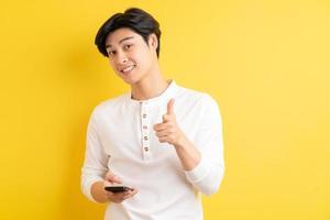 Aziatische man die zijn telefoon gebruikt en naar buiten wijst op een gele achtergrond foto