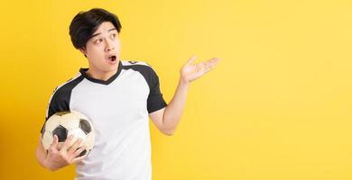 de Aziatische man hield de bal vast en wees met zijn hand opzij foto