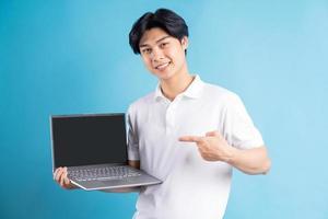 de Aziatische man wees met zijn vinger naar de laptop met een leeg scherm blank foto