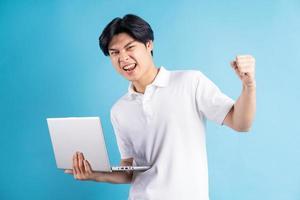 de Aziatische man hield zijn laptop vast en toonde een triomfantelijke uitdrukking foto