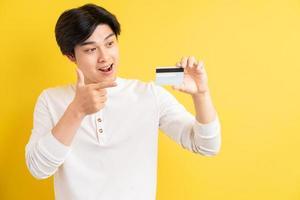 Aziatische man met een bankkaart in zijn hand op een gele achtergrond foto