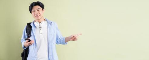 mannelijke Aziatische student lacht en wijst met zijn vinger naar de linkerkant foto