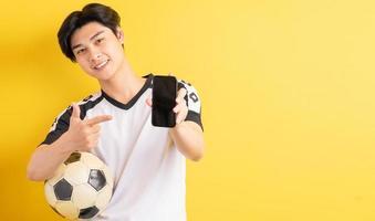 de aziatische man houdt een bal vast en wijst naar de telefoon met een leeg scherm foto