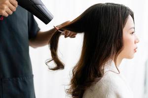 Aziatische vrouw met gelukkige uitdrukking die kappers doet bij salong foto