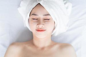 Aziatische vrouw doet schoonheidsbehandelingen, spabehandelingen en wordt crème op haar gezicht aangebracht foto