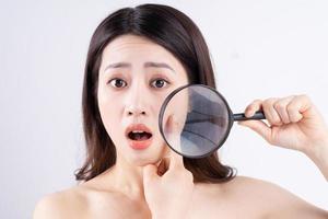 Aziatische vrouw met een verbaasde uitdrukking bij het verschijnen van acne foto