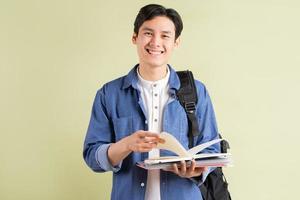 foto van een knappe Aziatische student die lacht en een boek in de hand houdt