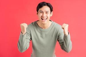 een foto van een knappe Aziatische man die zijn hand gebruikt om zijn overwinningsgevoelens te uiten