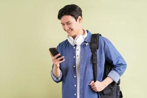 portret van knappe Aziatische student met behulp van slimme telefoon foto