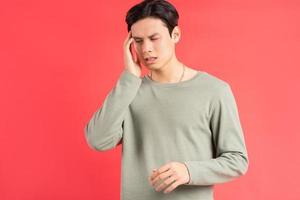 een foto van een knappe Aziatische man die met zijn hand over zijn hoofd wrijft vanwege zijn migraine