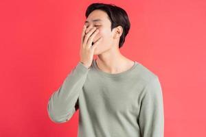 een foto van een knappe Aziatische man die geeuwt met zijn hand voor zijn mond