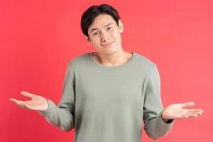 een foto van een knappe Aziatische man die verward zijn schouders ophaalt