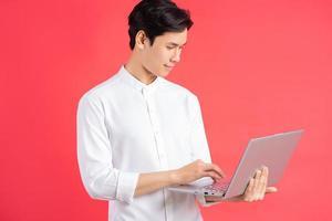 een foto van een knappe Aziatische man die op een rode achtergrond staat met een computer