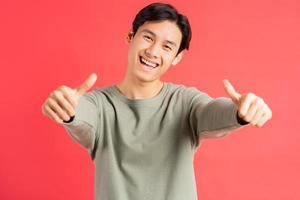 een foto van een knappe Aziatische man die 2 duimen omhoog houdt met een vrolijk gezicht