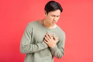 een foto van een knappe Aziatische man die zijn armen om zijn borst houdt vanwege een hartaanval