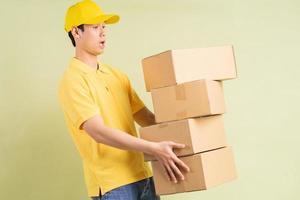 Aziatische bezorger houdt de doos bij zich en rent om de goederen af te leveren foto
