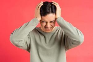 een foto van een knappe Aziatische man die vermoeid zijn hoofd met beide handen vasthoudt