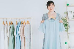 jonge aziatische mooie vrouw is live aan het streamen om kleding te verkopen op sociale netwerkplatforms en e-commercesites. dit wordt de toekomstige trend van de e-commerce-industrie foto