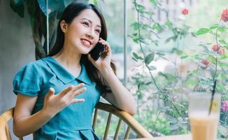 jonge aziatische vrouw die smartphone gebruikt bij coffeeshop foto