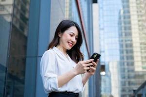 jonge Aziatische vrouw die smartphone gebruikt om naar haar vrienden te sms'en foto