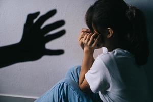 Aziatische vrouw knuffelt haar gezicht en huilt vanwege het geweld van haar vriend foto