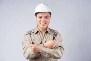 Aziatische reparateur permanent met gevouwen armen op grijze achtergrond foto