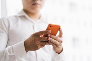 Aziatische zakenman die smartphone bij het raam gebruikt foto