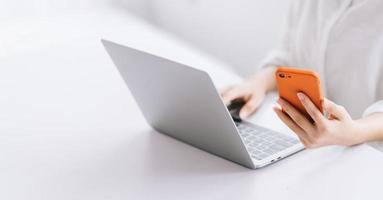 bijgesneden afbeelding van Aziatische zakenvrouw met behulp van laptop foto